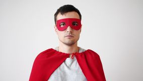 Portrait of young man in superman costume red mask and cape looking at camera. With serious face standing alone. People, lifestyle and superhero concept stock video footage