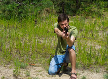 Portrait of a young man taking aim with a pneumatic gun royalty free stock photography