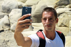 Portrait of young man taking selfie by cell, mobile phone , smartphone on on mountain Royalty Free Stock Photography