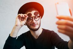 Portrait of young man taking selfie, standing over white background. Dressed in black, wearing sunglasses and hat. Portrait of young man taking selfie, standing stock photo