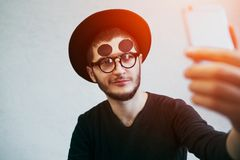 Portrait of young man taking selfie, standing over white background. Dressed in black, wearing sunglasses and hat. Portrait of young man taking selfie, standing stock photos