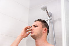Portrait of young man taking a shower in the bathroom. Portrait of young man taking a shower, standing under flowing water in shower cabin in the modern tiled Royalty Free Stock Image