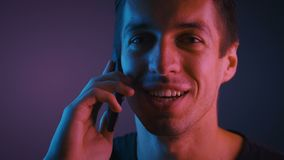 Portrait of a young man talking on a cell phone in a room lit by a neon light stock video footage
