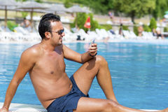 Portrait of young man talking on the phone on the pool Stock Images