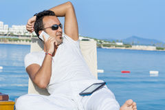 Portrait of young man talking on the phone on a sea background Stock Photos