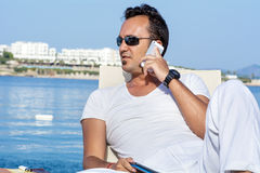 Portrait of young man talking on the phone on a sea background Stock Images