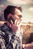 Portrait of young man talking by phone. Vintage filtered image. Royalty Free Stock Images