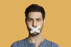 Portrait of a young man with tape on mouth over colored background Royalty Free Stock Photo