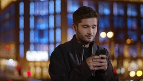 Calm man texting mobile phone on dark street. Relaxed guy typing smartphone