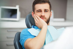 Portrait of young man with tooth pain sitting in a dentist's cha Stock Photo