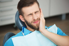 Portrait of young man with tooth pain sitting in a dentist's cha Stock Image