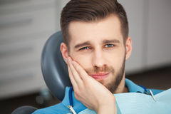 Portrait of young man with tooth pain sitting in a dentist's cha. Shot of a young man with tooth pain while sitting in a dentist's chair stock image