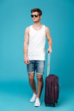 Portrait of a young man tourist in sunglasses with suitcase Stock Photo