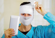 Portrait of a young man with trauma in his head and elastic bandaged around his head holding a tablet Royalty Free Stock Photos
