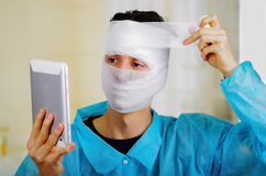 Portrait of a young man with trauma in his head and elastic bandaged around his head holding a tablet Stock Images