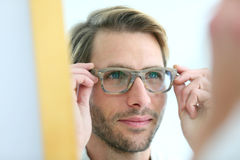 Portrait of young man trying on eyeglasses Royalty Free Stock Images