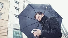 Young man in coat with umbrella under snowfall using smartphone on alley. Portrait of young man with an umbrella under a snowfall using a smartphone. Snowy city stock video footage