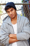 Portrait Of Young Man In Urban Setting Standing By Fence Royalty Free Stock Image