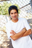 Portrait Of Young Man In Urban Setting Standing By Fence Royalty Free Stock Photos