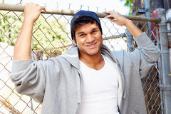 Portrait Of Young Man In Urban Setting Standing By Fence Royalty Free Stock Images