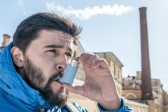 Portrait of young man using asthma inhaler outdoor. With factory chimney on backgroung royalty free stock images