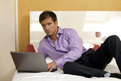 Portrait of young man using laptop on bed Royalty Free Stock Photos