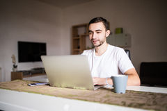 Portrait of young man using laptop while having breakfast in the morning Royalty Free Stock Photos
