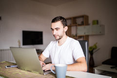 Portrait of young man using laptop while having breakfast in the morning Royalty Free Stock Images