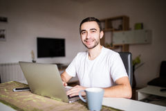 Portrait of young man using laptop while having breakfast in the morning Stock Photos