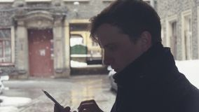 Portrait of young man in knitted scarf using smartphone on street under snowfall. Portrait of young man using smartphone, typing sms, scrolling pictures standing stock video
