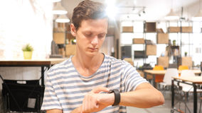 Portrait of Young Man Using smartwatch, royalty free stock photo