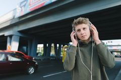 Portrait of a young man walking in the city on the background of urban architecture and listening to music in headphones. On the b Royalty Free Stock Photos
