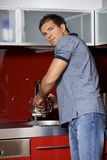 Portrait of young man washing his hands in sink Royalty Free Stock Photo