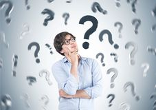 Pensive young man in glasses, question marks Royalty Free Stock Image