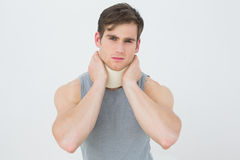 Portrait of a young man wearing cervical collar. Over white background stock photography