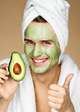 Portrait of young man wearing facial mask holding slice of avocado and showing thumb up Royalty Free Stock Photography