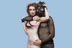 Portrait of young man wearing gas mask embraces funky woman over blue background Stock Photography
