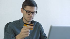 Young man using credit card online. Portrait of a young man wearing glasses sitting in front of a monitor - making a purchase using a credit card online. People stock footage
