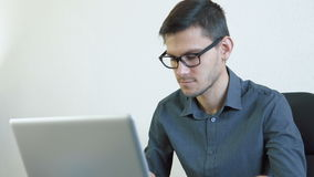 Young man using credit card online. Portrait of a young man wearing glasses sitting in front of a monitor - making a purchase using a credit card online. People stock video footage