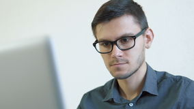 Young man using credit card online. Portrait of a young man wearing glasses sitting in front of a monitor - making a purchase using a credit card online. People stock video