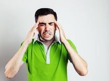 Portrait of young man wearing green shirt having head pain Royalty Free Stock Images