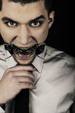 Portrait of young man wearing grey shirt and tie, with bdsm spider in mouth Stock Photo