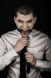 Portrait of young man wearing grey shirt and tie, with bdsm spider in mouth Royalty Free Stock Photo