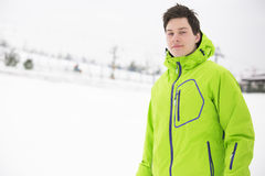 Portrait of young man wearing hooded jacket in snow Stock Photography