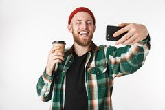 Portrait of young man wearing plaid shirt holding paper cup with coffee and using mobile phone, while standing isolated over white. Portrait of young man wearing stock photography
