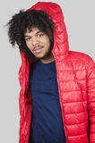 Portrait of young man wearing red jacket with hood over colored background Stock Photo