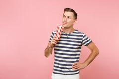 Portrait of young man wearing striped t-shirt holding plastic cup of soda, red glass cola isolated on trending pastel. Pink background. People youth sincere royalty free stock image