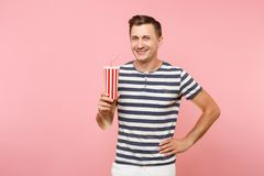 Portrait of young man wearing striped t-shirt holding plastic cup of soda, red glass cola isolated on trending pastel. Pink background. People youth sincere royalty free stock images