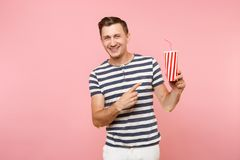 Portrait of young man wearing striped t-shirt holding plastic cup of soda, red glass cola isolated on trending pastel. Pink background. People youth sincere royalty free stock photography