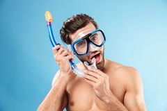 Portrait of a young man wearing swimming mask and snorkel. Portrait of a young handsome man wearing swimming mask and snorkel isolated over blue Stock Images